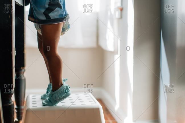 Close-up of a toddler standing on a stool next to the bathroom sink