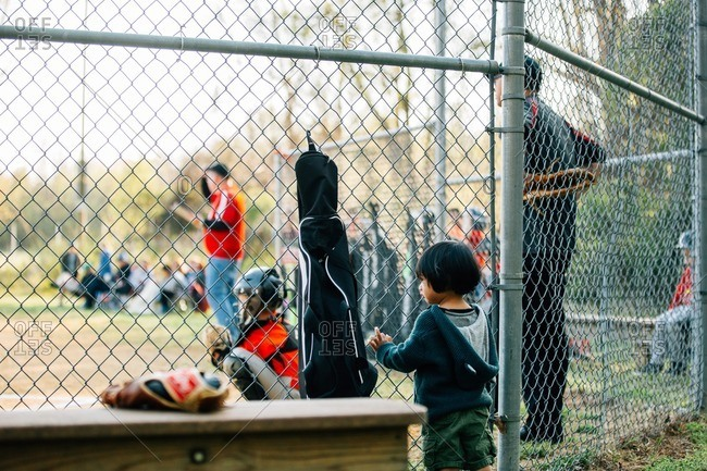 Child standing at a backstop fence during a baseball game