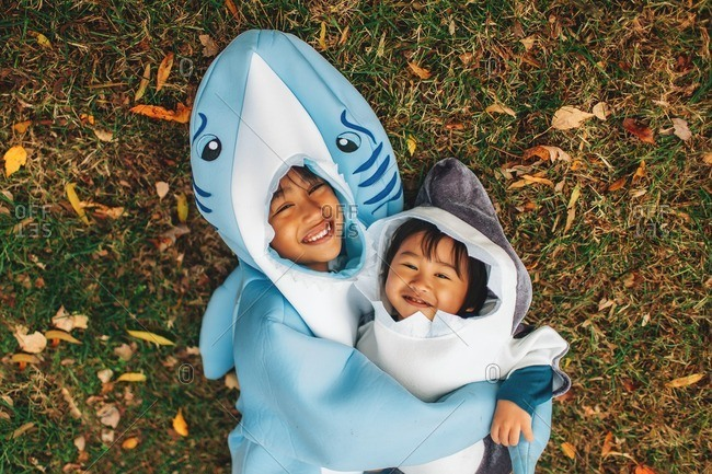 Two children dressed in shark costumes playing together outside