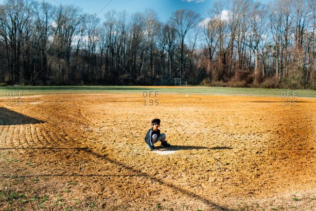 Boy sitting alone on a baseball diamond