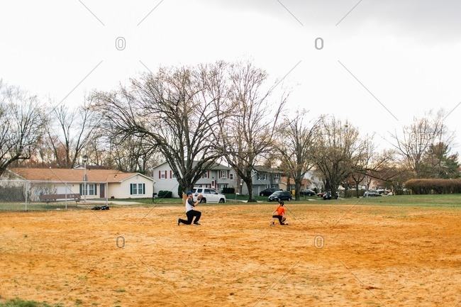 Father playing baseball with his son at a local park