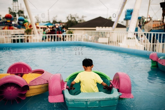 Boy sitting in a paddleboat at a carnival