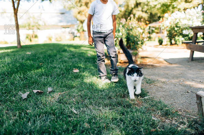 Boy walking outside with a cat