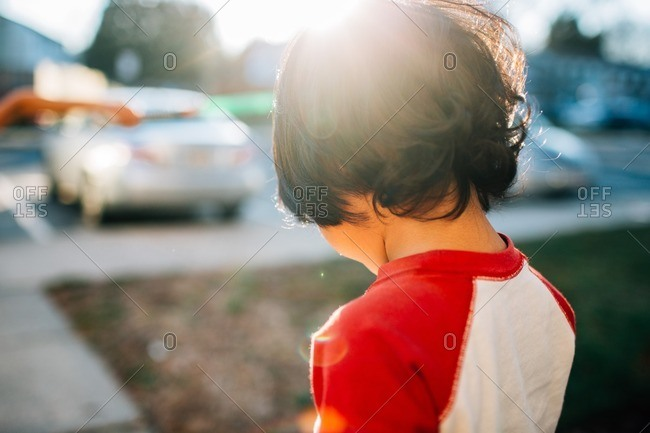 Young boy standing outside on a sunny day