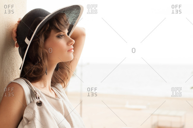 Woman in a hat leaning against wall