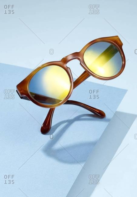 Sunlight reflected in pair of sunglasses on blue background