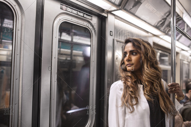 Close-up of thoughtful woman traveling in subway train
