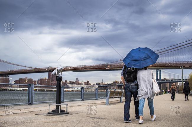 People walking on footpath by East River against Brooklyn bridge during storm