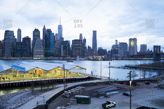 Basketball court by commercial dock against East River during stormy weather
