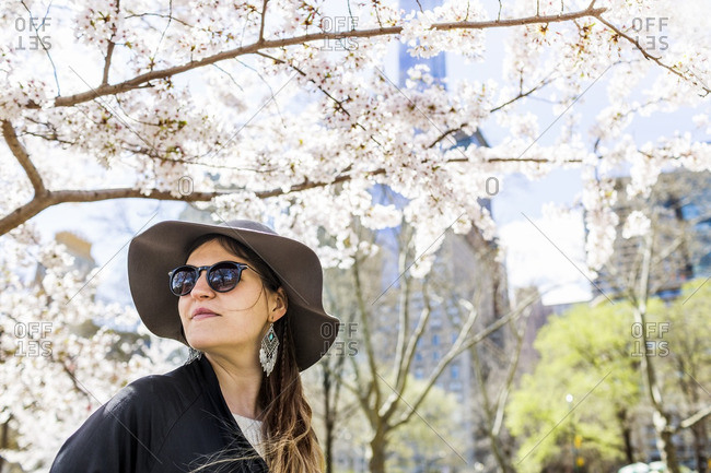Close-up of woman looking away against flowering tree at Central Park