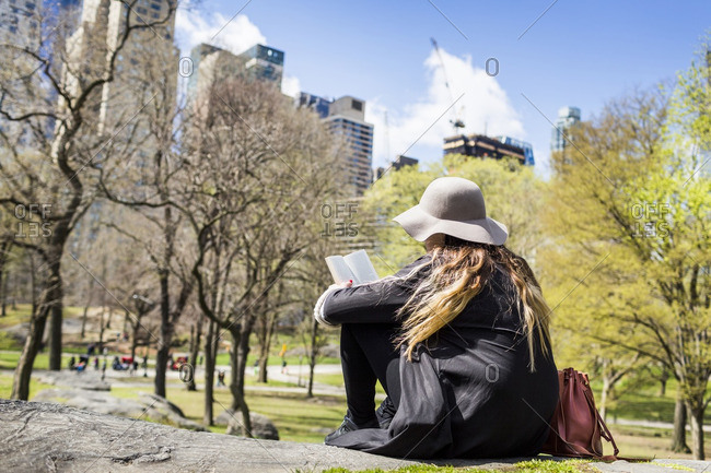 Rear view of woman reading book while sitting on rock at Central Park