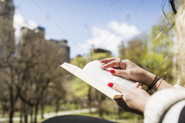 Cropped image of woman reading book at Central Park