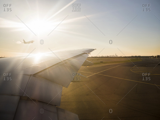 Cropped image of airplane on airport runway against shining sun