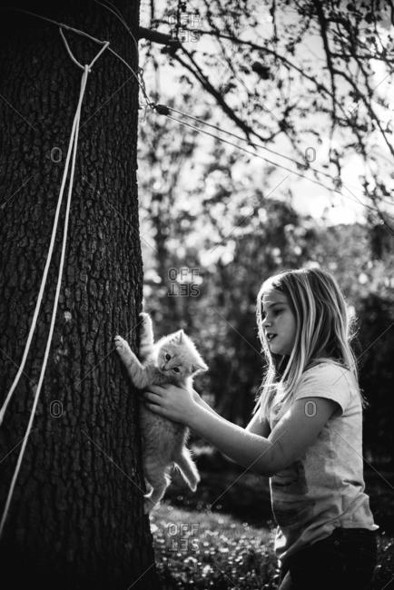 Young girl with pet kitten on tree