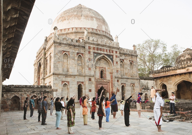New Delhi, India - September 25, 2008: Young men and women practicing early morning yoga at the Bara-Gumbad Tomb