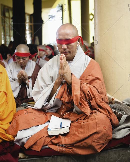McLeod Ganj, Dharamsala, India - October 3, 2008: A monk prays during a Tibetan Chenrezig Initiation