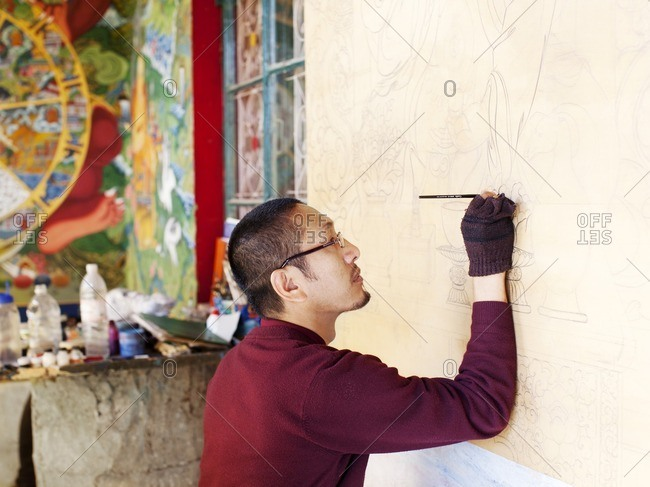 McLeod Ganj, Dharamsala, India - October 9, 2008: A Tibetan monk paints a mural on a wall at the entrance to the Tibetan Library of Works and Archives