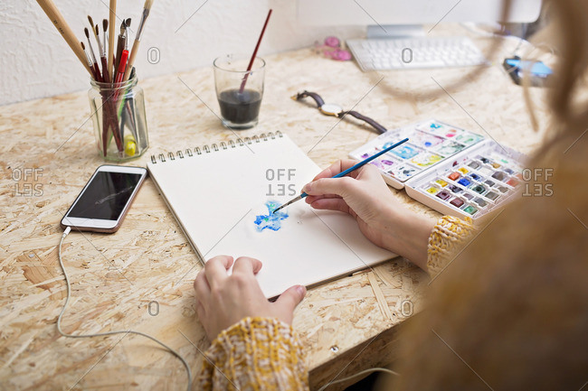 Woman painting with watercolors at table
