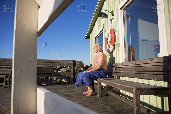 Man wrapped in towel sitting on bench in warm sunlight