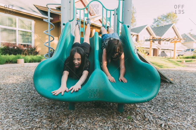 Two young girls sliding headfirst down slide