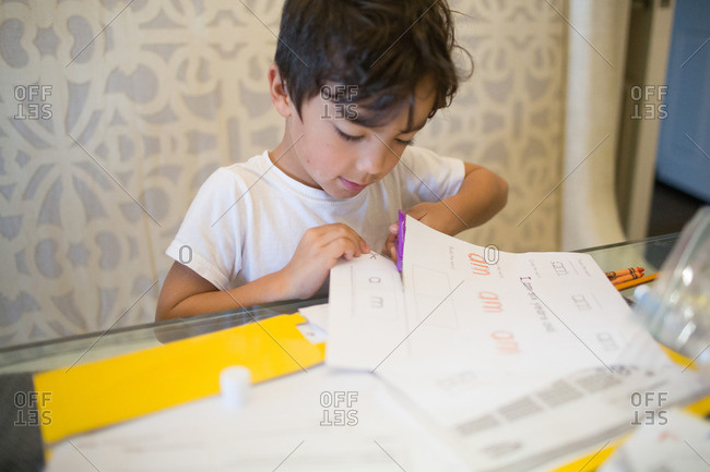Young boy cutting paper at table