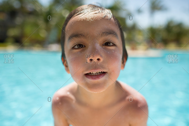 Close-up of a wet young boy in a pool