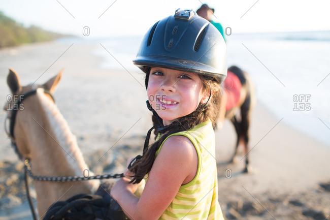 Young girl in helmet on a horseback ride on beach