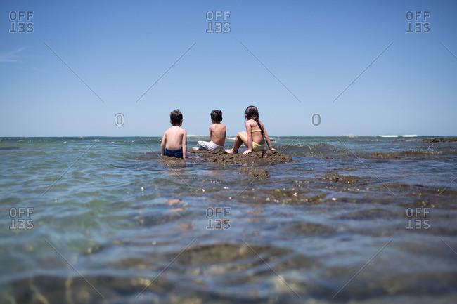 Three children sitting on rocks in the ocean