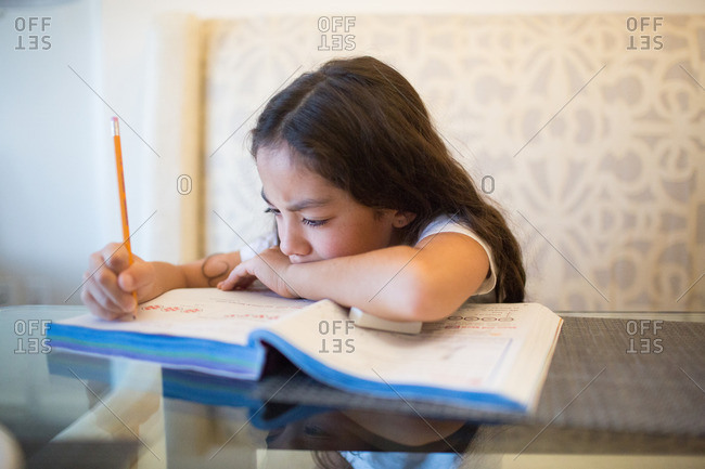 Young girl concentrating while writing in her workbook