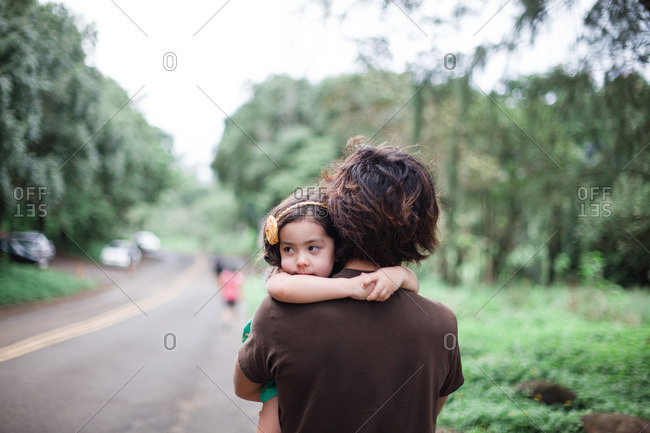 Young girl being carried by her father as they walk down a road