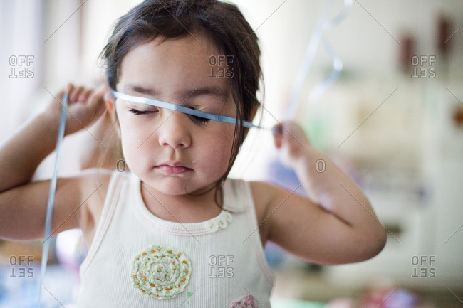 Young girl playing with a ribbon