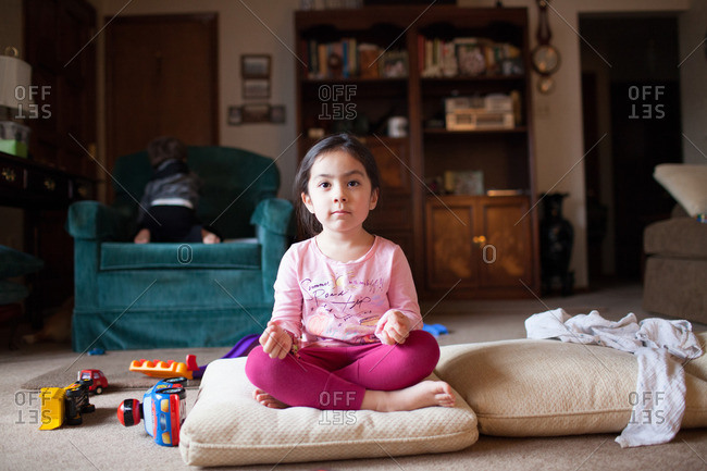 Young girl sitting on a pillow in lotus position