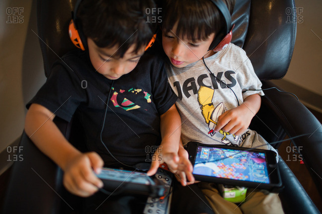 Two young boys playing games on tablets while wearing headphones