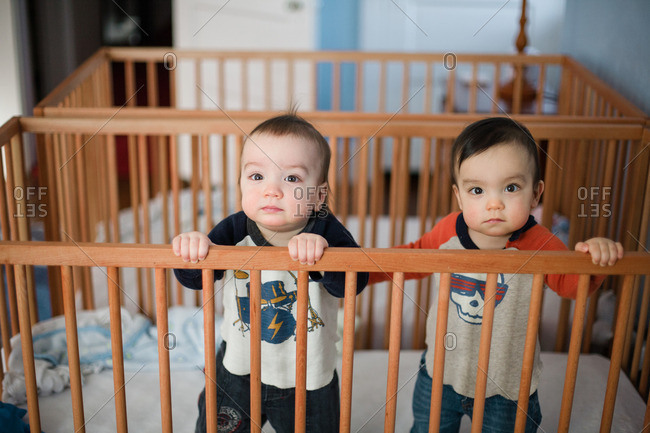 Twin toddler boys together in crib