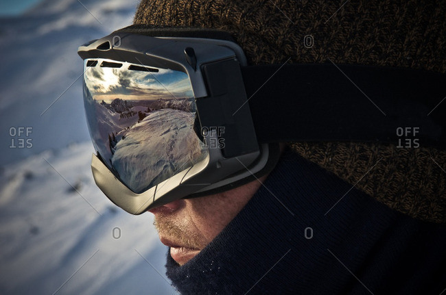 Snowy mountain landscape at dusk reflected in a skier's goggles
