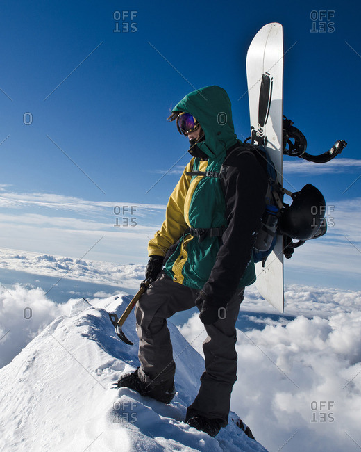 Mountaineer with snowboard standing at the summit of a mountain