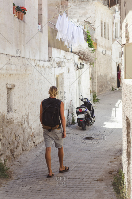 Tourist walking down narrow street between buildings in Turkey