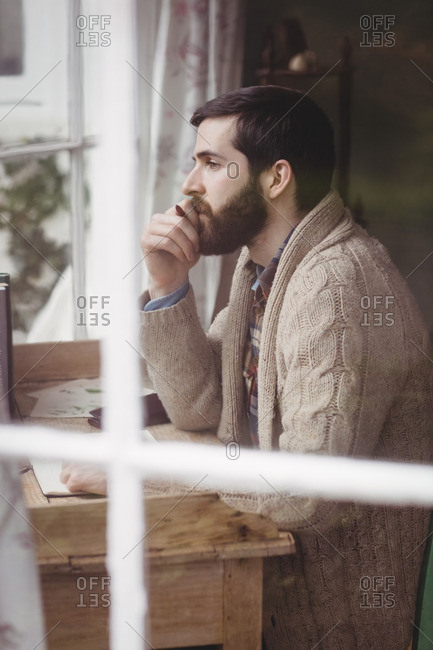 Profile view of attractive hipster man looking through window