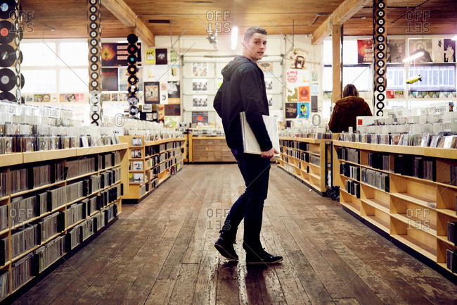 Young man holding vinyl record in music store