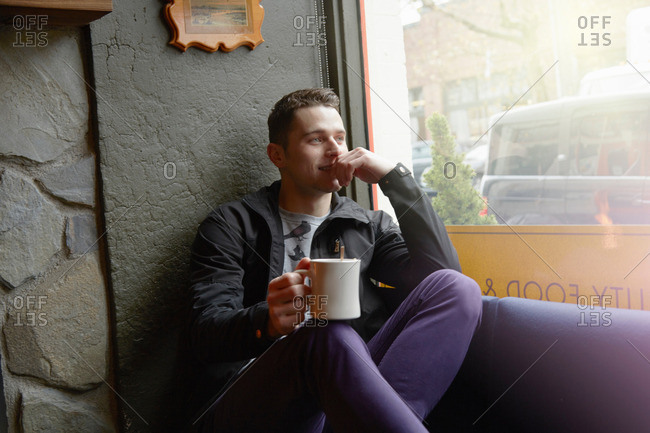 Young man sitting in cafe window seat looking out of window