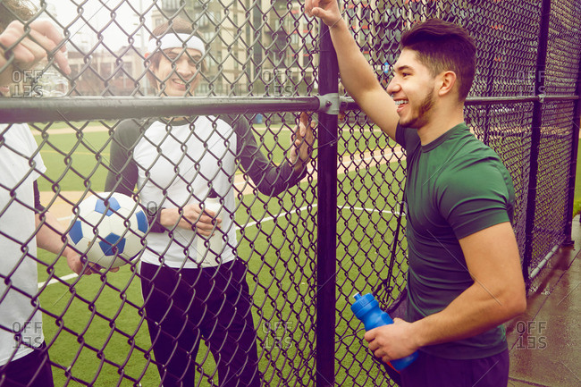 Three male soccer players chatting through wire fence