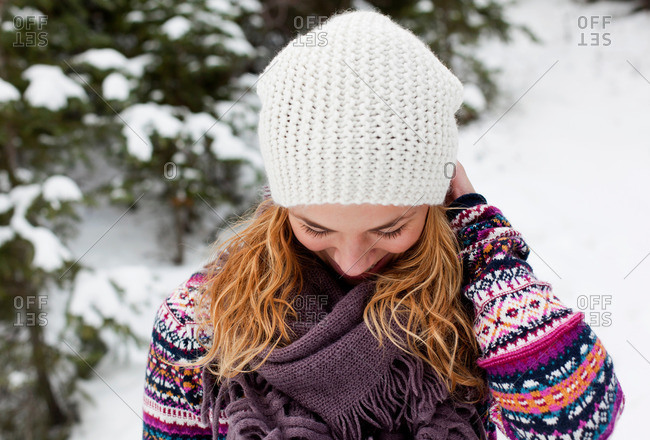 Young woman giggling in front of snow covered fir trees