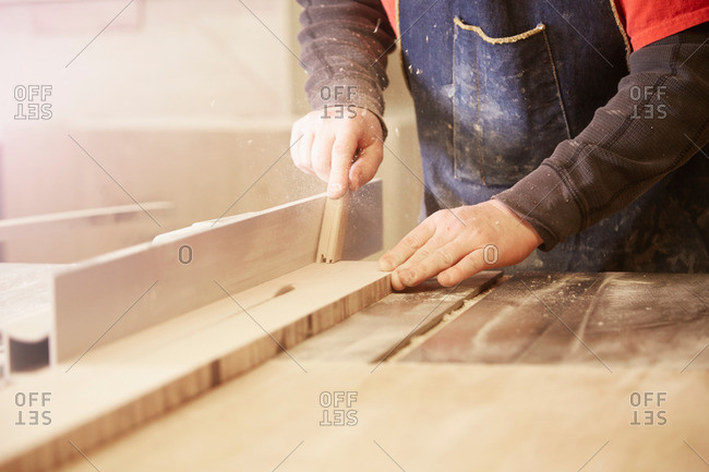 Close up of cabinet maker using table saw in workshop