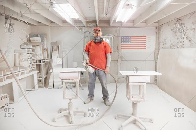 Portrait of cabinet maker with spray gun in workshop spray booth