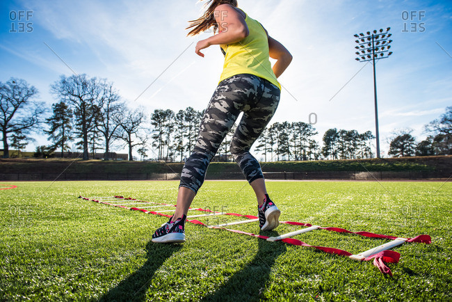 Female athlete training with agility ladder on sports field