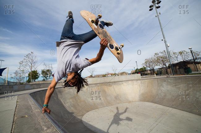 Young man doing skateboard trick upside down on edge of skateboard park