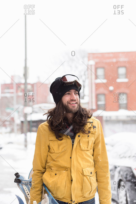 Smiling male snowboarder in snow covered street