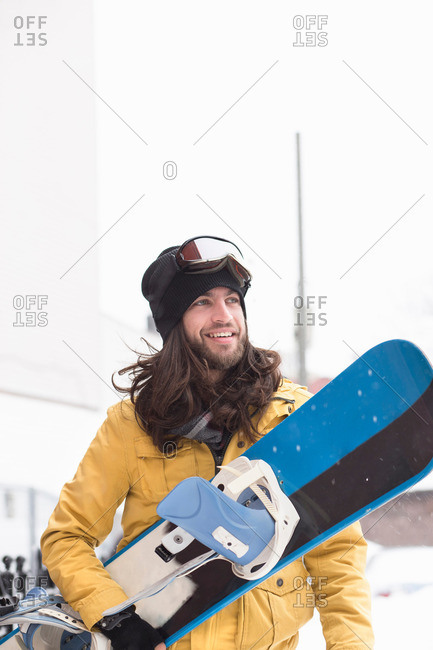 Smiling male snowboarder carrying snowboard in street