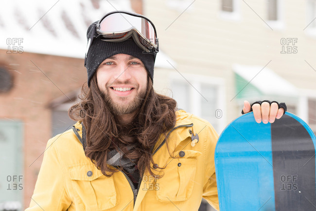 Portrait of young man holding snowboard on street