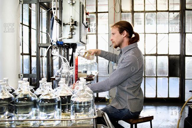 Young male vodka distiller pouring liquid into cylinder in distillery workshop